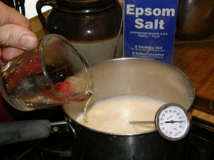 Bring the soy milk (filtrate) back to a boil. Dissolve 1 tablespoonfull of Epsom salts (MgSO4.7H2O) in ½ cup warm water.    [Traditional recipes call for CaSO4 or MgCl2.  Since I had neither, but did have epsom salts which is the first cousin of each of these salts, I decided to try it as a coagulant.  It worked great.]  Remove boiling soy milk from heat, add in Epsom salts solution with much stirring.