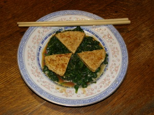 "Store in the fridge in fresh water for up to three days.  Best if used fresh. One of our favorite ways to eat tofu is to ""bread"" it with brewer's yeast, fry it till brown on both sides, and serve with soy sauce.  Here it is served on sauted kale with ginger and garlic."